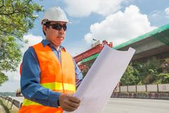 Engineer or Architect wear white Helmet working or reading Construction Plan. In Highway or Autobahn Construction site as Industrial or infrastructure royalty free stock photos