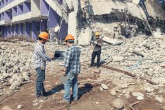 Engineer architect and worker operation control demolish old building. Vintage effect.  royalty free stock image