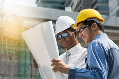 Engineer and Architect working at Construction Site with bluepri. Nt,man Stock Image