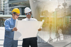 Engineer and Architect working at Construction Site. With blueprint Royalty Free Stock Images