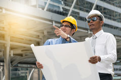 Engineer and Architect working at Construction Site. With blueprint Stock Photo