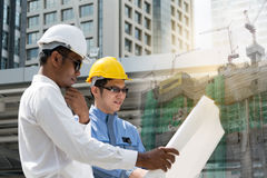 Engineer and Architect working at Construction Site. With blueprint Stock Image