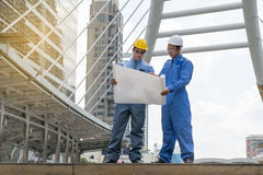 Engineer and Architect working at Construction Site. With blueprint Royalty Free Stock Photo
