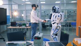 An engineer in augmented reality glasses and a robot are shaking hands. 4K stock video footage