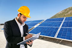 Engineer with big solar panels on background. Royalty Free Stock Images