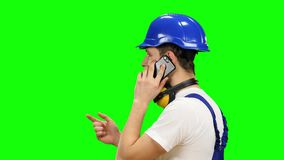 Engineer in a blue helmet speaks on the phone and shows a thumbs up. Green screen stock video