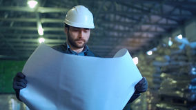 An engineer with blueprint. An architect looking in the blueprint and smiling in the warehouse Stock Photos