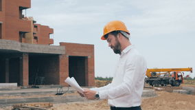 Engineer with blueprint at construction site. Master builder in hard hat. stock video footage