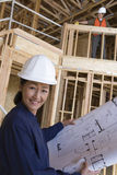 Engineer With Blueprint At Site Stock Photo