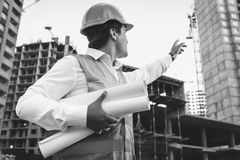 Engineer with blueprints checking building site construction Stock Images