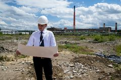 Engineer with blueprints on site. Young engineer on site. He is holding blueprints in his hand Stock Photos