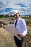 Engineer with blueprints on site. Young engineer on site. He is holding blueprints in his hand Royalty Free Stock Images