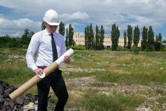 Engineer with blueprints on site. Young engineer thinking on site. He is holding blueprints in his hand Stock Image