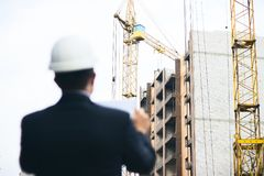 Engineer boss with protective safety helmet checking architectural drawing at construction site. Royalty Free Stock Photos