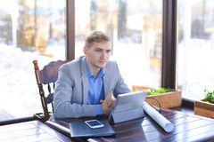Engineer browsing with tablet and sitting at cafe with smartphon. Engineer browsing by tablet and sitting at cafe with smartphone, roll project and black stock photo