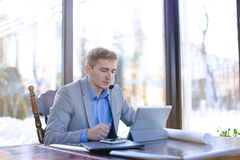Engineer browsing with tablet and sitting at cafe with smartphon. Engineer browsing by tablet and sitting at cafe with smartphone, roll project and black Royalty Free Stock Photos