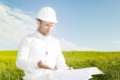 Engineer builder is dissatisfied with poor project documentation. Worker with blueprints on background of meadow. And blue sky with white clouds during day Stock Photography