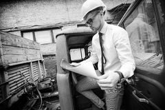Engineer builder in a helmet holds drawings at  construction site Royalty Free Stock Images
