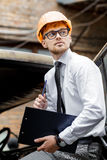 Engineer builder in a helmet holds drawings at  construction site Stock Image