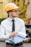 Engineer builder in a helmet holds drawings at construction site Stock Images