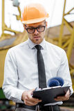 Engineer builder in a helmet holds drawings at construction site Royalty Free Stock Photography