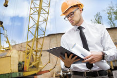 Engineer builder in a helmet holds drawings at construction site Royalty Free Stock Photo