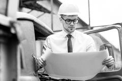 Engineer builder in a helmet holds drawings at  construction site Royalty Free Stock Image