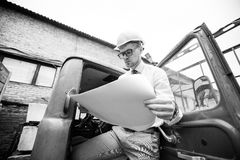 Engineer builder in a helmet holds drawings at  construction site Royalty Free Stock Photos