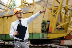 Engineer builder in a helmet holds drawings and shows by hand at construction site Royalty Free Stock Image