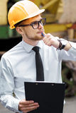 Engineer builder in a helmet holds folder at construction site Royalty Free Stock Images