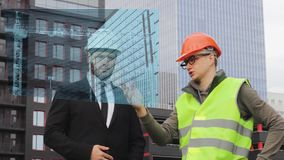 Engineer and builder hologram discuss drawing new technologies virtual  business. Engineer and builder check hologram discuss drawing new technologies virtual stock footage