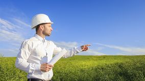 Engineer builder in white helmet and with blueprints on green field background on bright sunny day pointing his hand to distance. Designer points to place of Stock Image