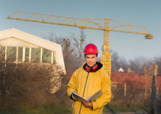 Engineer on building site. Young engineer smiling and making notes on building site with crane in background Royalty Free Stock Photos