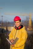 Engineer on building site. Young engineer smiling and making notes on building site with crane in background Royalty Free Stock Images