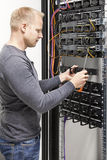 IT engineer builds network rack in datacenter. IT consultant or technician working with network cabling and installation communication switches in datacenter stock photo