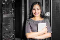 Engineer businesswoman in network server room. Young engineer businesswoman with tablet in network server room Royalty Free Stock Images