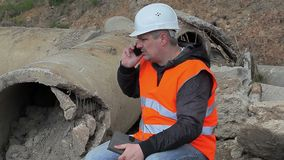 Engineer with cell phone at the broken concrete pipe stock video