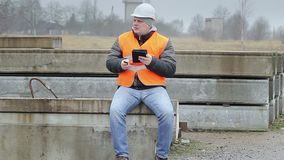 Engineer with cell phone and tablet PC on the concrete panels stock video footage