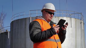 Engineer with cell phone and tablet PC near oil tank stock footage