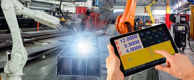 Engineer check and control welding robotics automatic arms machine in intelligent factory automotive industrial with monitoring. System software. Digital stock photography