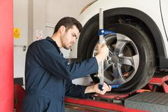 Engineer Checking Alignment Of Tire With Camber Caster Adapter. Maintenance engineer checking alignment of tire with camber caster adapter in garage royalty free stock image