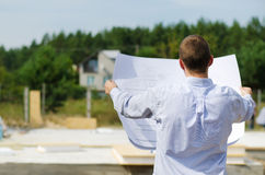 Engineer checking a building plan on site. View from behind of a young architect or engineer checking a building plan on site holding it open in his hands as Stock Images