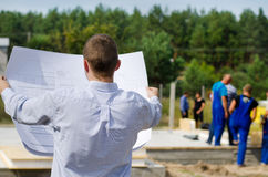Engineer checking a building plan on site. View from behind of a young architect or engineer checking a building plan on site holding it open in his hands as Royalty Free Stock Images