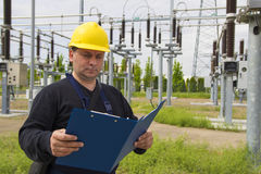 Engineer is checking high voltage transformerstation. Technician with yellow helmet inspect high voltage power station stock photo