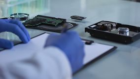 Engineer checking microcircuit and filling report, computer board repair, chip. Stock footage stock footage
