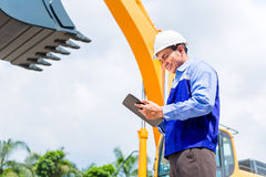 Engineer checking plans on construction site Royalty Free Stock Image