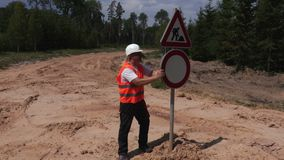 Engineer checking road signs. In summer day stock footage