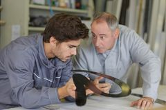 Engineer checking trainees work on factory floor royalty free stock image