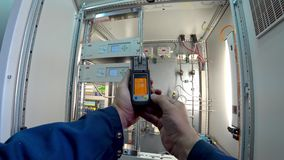 Engineer checks the gas level of the personal gas analyzer Drager at his workplace in the ABB gas analyzer cabinet. Action camera stock video footage
