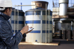 Engineer cheking plant. Looking storage tank Stock Photography